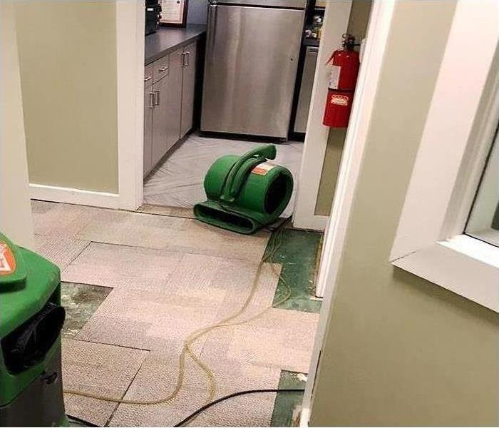 Air movers and dehumidifiers setup to restore water damage to Manhattan office kitchen