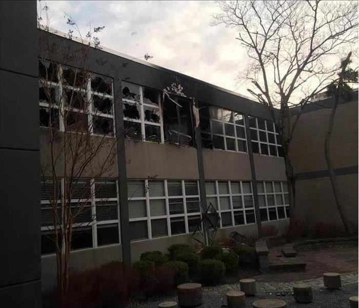 School exterior with fire damage including broken windows and smoke and soot damage
